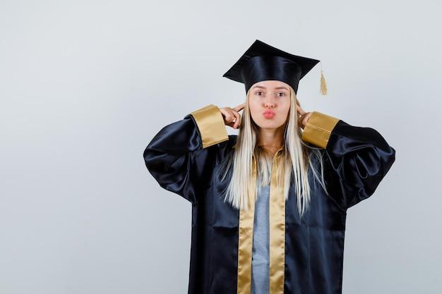 卒業式のガウンとキャップのブロンドの女の子が人差し指で耳を塞ぎ、キスを送り、かわいく見える