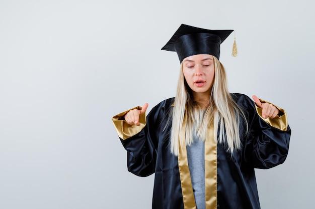 人差し指でカメラを指して真剣に見える卒業式のガウンとキャップのブロンドの女の子