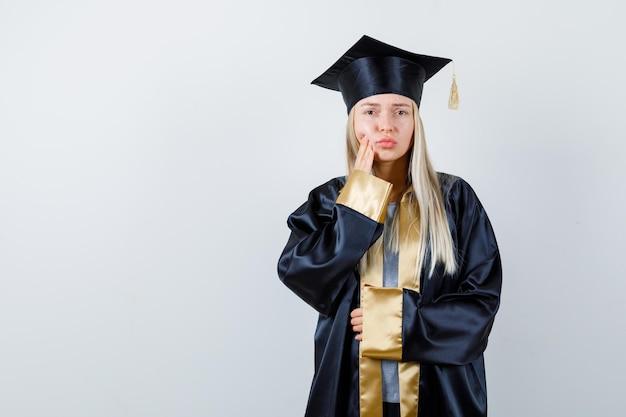 卒業式のガウンとキャップのブロンドの女の子は、片方の手を口の近くに置き、もう一方の手を腹に抱き、歯痛を抱え、疲れ果てているように見えます