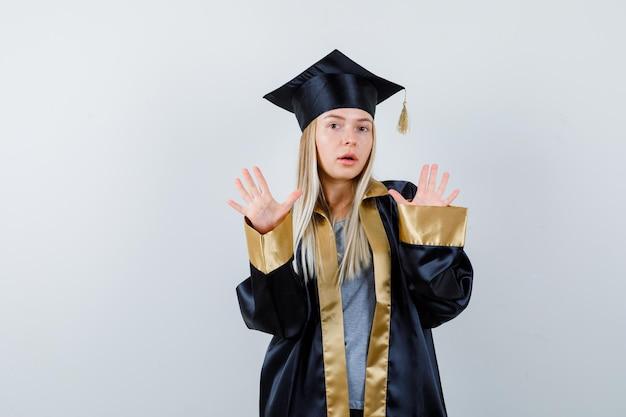 Блондинка в выпускном платье и кепке поднимает руки в позе капитуляции и выглядит испуганной
