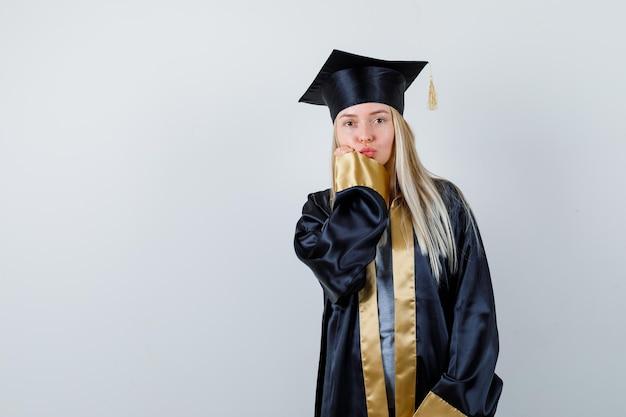 Блондинка в выпускном платье и кепке посылает поцелуи и прикладывает руку ко рту и выглядит мило