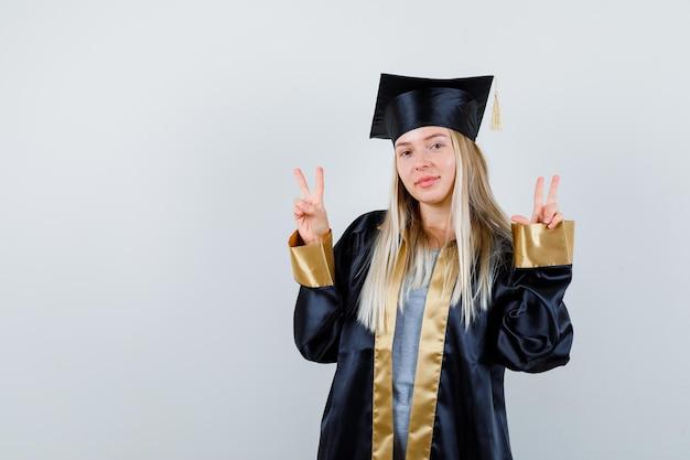 平和のジェスチャーを示し、かわいく見える卒業ガウンとキャップのブロンドの女の子