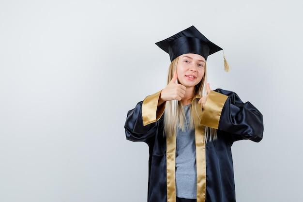 卒業式のガウンとキャップのブロンドの女の子が両手で親指を上げて幸せそうに見える