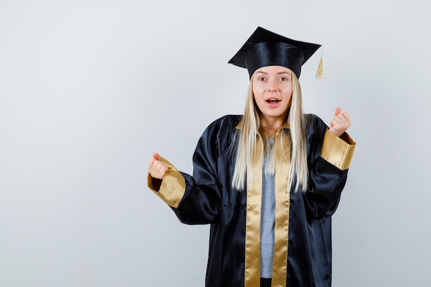 卒業式のガウンとキャップのブロンドの女の子が勝者のジェスチャーを示し、幸せそうに見えます