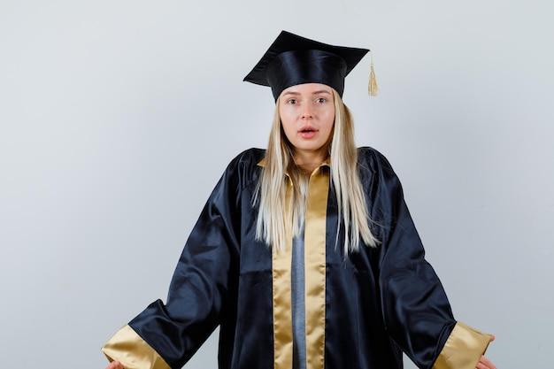 卒業式のガウンとキャップのブロンドの女の子は肩をすくめて、困惑しているように見えます