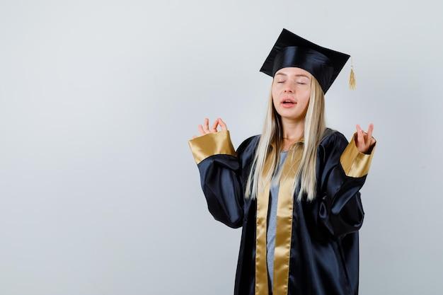 瞑想のポーズで立って、落ち着いて見える卒業式のガウンとキャップのブロンドの女の子