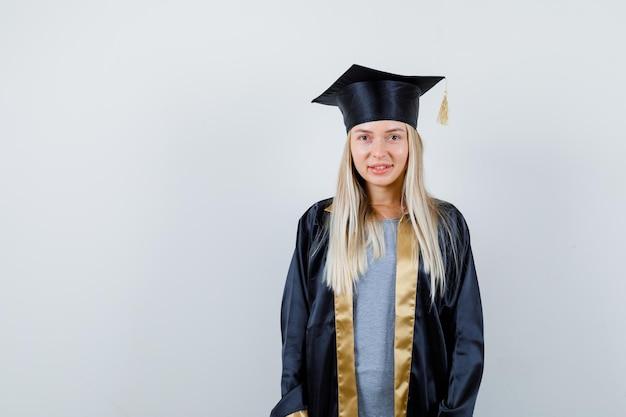 卒業式のガウンとキャップのブロンドの女の子がまっすぐ立ってカメラに向かってポーズをとってかわいい