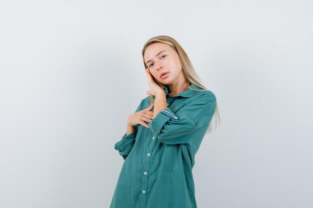 緑のブラウスのブロンドの女の子は、胸に手を握り、輝くように見えながら頬に手を置きます