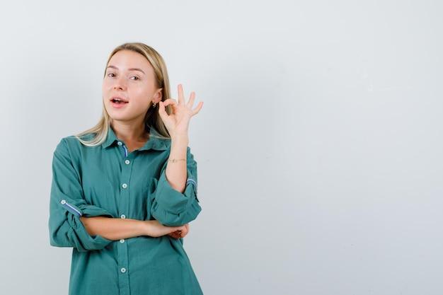 Блондинка в зеленой блузке показывает знак ок, держась за локоть и выглядит счастливой