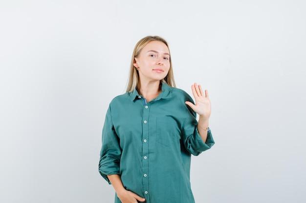 Блондинка в зеленой блузке показывает знак остановки, держа руку на животе и выглядит красиво