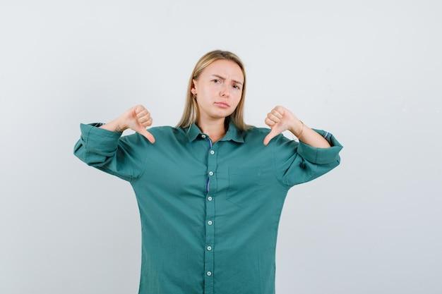 Блондинка в зеленой блузке показывает палец вниз обеими руками и выглядит недовольным