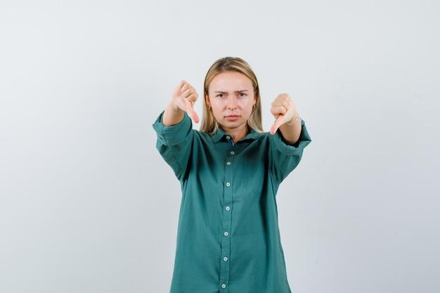 두 손으로 아래로 엄지 손가락을 보여주는 녹색 블라우스에 금발 소녀