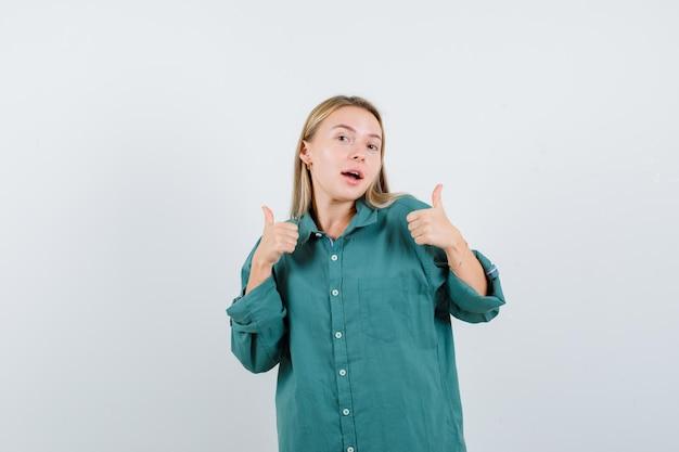 Блондинка в зеленой блузке показывает палец вверх обеими руками и выглядит красивой