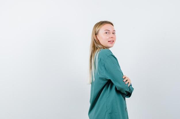 녹색 블라우스 서 팔에 금발 소녀 넘어, 어깨 너머로보고 예쁜 찾고