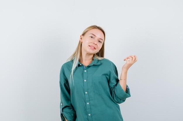 Блондинка в зеленой блузке протягивает одну руку, держа что-то и выглядит счастливой