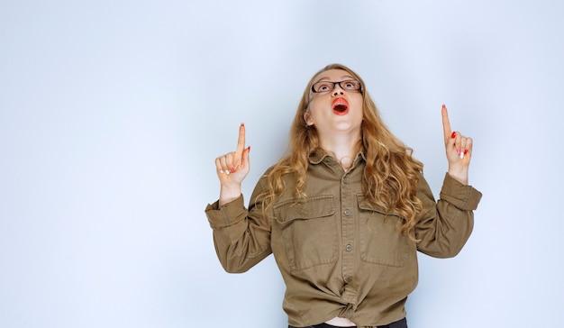 위에 가리키는 녹색 셔츠에 금발 소녀입니다. 무료 사진