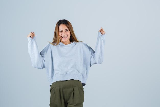 オリーブグリーンブルーのスウェットシャツとパンツのブロンドの女の子は、勝者のジェスチャーを示し、幸せそうに見える、正面図。