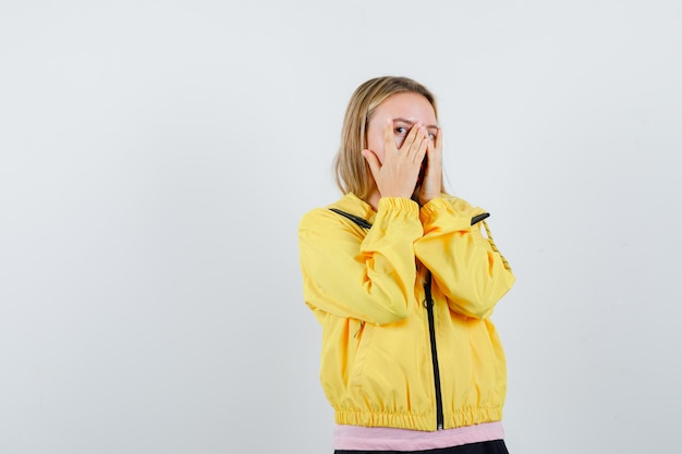 ピンクのtシャツと黄色のジャケットのブロンドの女の子が手で顔を覆い、指を通して見て、魅力的に見えます