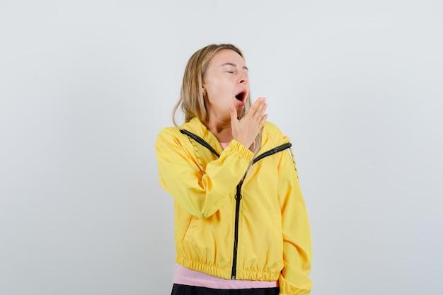 ピンクのtシャツと黄色のジャケットのブロンドの女の子が口の近くで手を握って、あくびをして眠そうに見えます