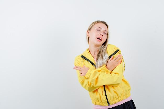 ピンクのtシャツと黄色のジャケットのブロンドの女の子は、2つの腕を組んで、兆候を身振りで示し、真剣に見えます