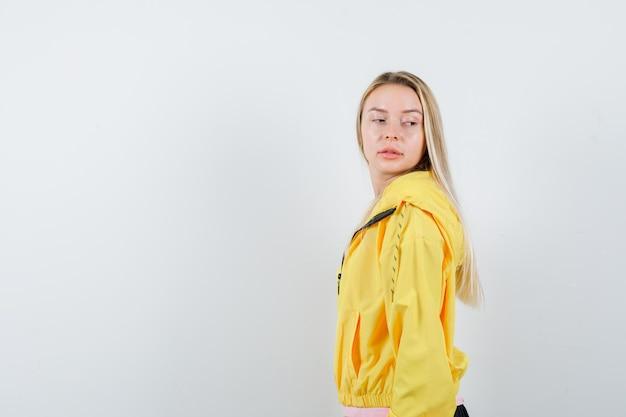 ピンクのtシャツと黄色のジャケットのブロンドの女の子がカメラにポーズをとって魅力的に見ながら肩越しに見ています