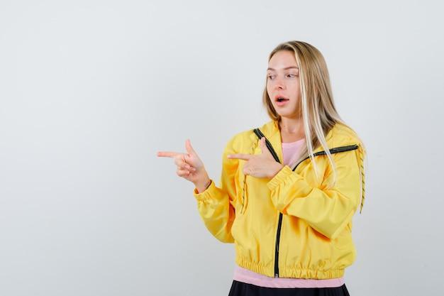 ピンクのtシャツと黄色のジャケットのブロンドの女の子が人差し指で左を指して魅力的に見えます