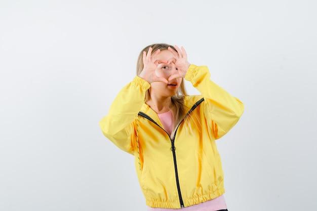 ピンクのtシャツと黄色のジャケットのブロンドの女の子が手で愛のジェスチャーを示し、魅力的に見える