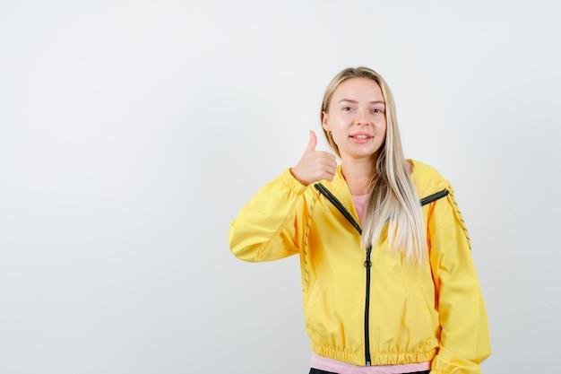 ピンクのtシャツと黄色のジャケットのブロンドの女の子が親指を立てて満足そう