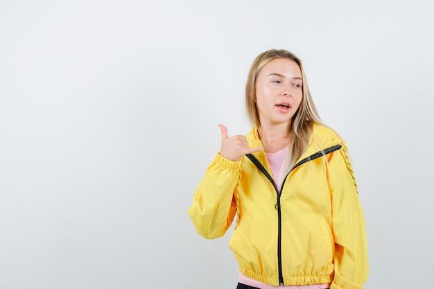 ピンクのtシャツと黄色のジャケットを着たブロンドの女の子が親指を立てて、目をそらし、物思いにふける