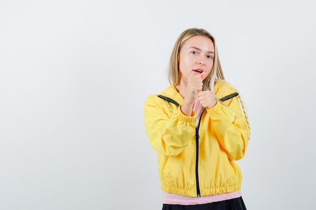 ボクサーのポーズで立って、パワフルに見えるピンクのtシャツと黄色のジャケットのブロンドの女の子