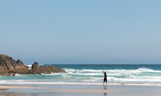 Блондинка в спортивной одежде вытягивает спину, наблюдая за волнами на берегу моря