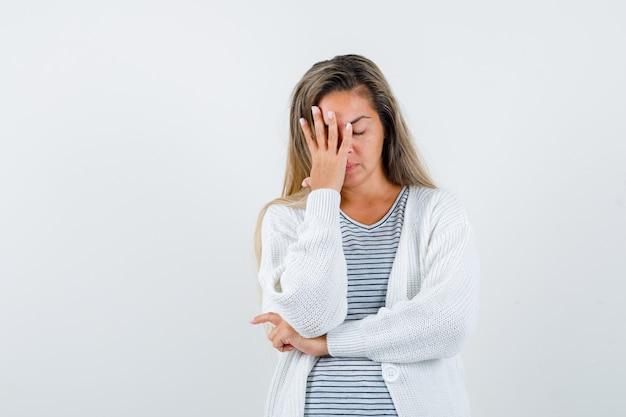 Блондинка в полосатой футболке, белом кардигане и джинсовых штанах закрывает часть лица рукой, держа руку под локтем и выглядит усталой, вид спереди.