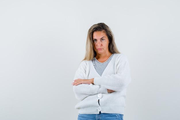 스트라이프 티셔츠, 흰색 카디건 및 진 바지에 금발 소녀가 팔을 서 교차하고 심각한, 전면보기를 찾고 있습니다.