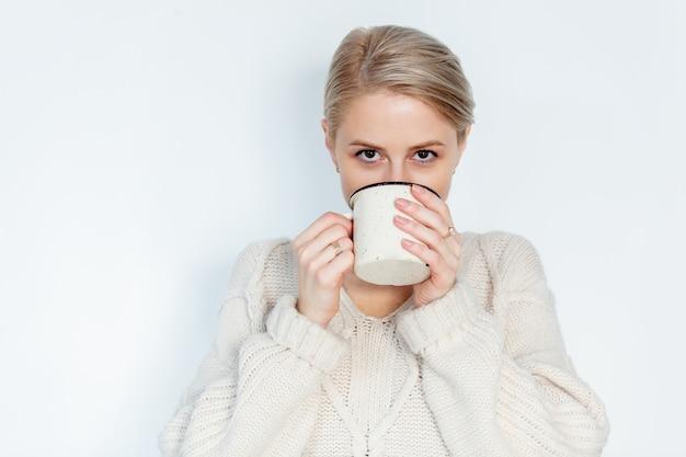 白のマグカップとセーターのブロンドの女の子