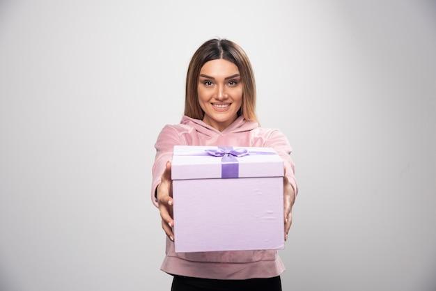 ギフトボックスを提供するスウェットシャツのブロンドの女の子。