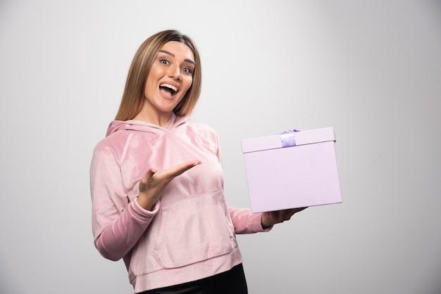 운동복을 입은 금발 소녀가 선물 상자를 받고 긍정적으로 놀라움을 느낍니다.