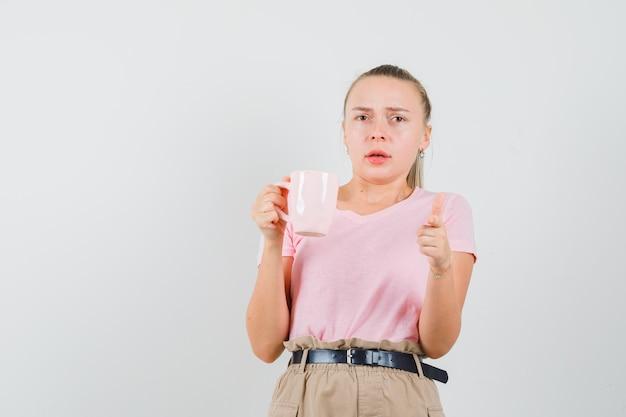 Tシャツを着たブロンドの女の子、飲み物のカップを保持し、正面を指して、心配そうに見える、正面図。