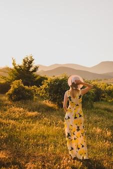 Блондинка в сельской местности в шляпе и красивом платье на закате