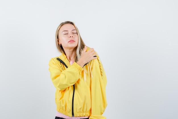 어깨에 손을 잡고 편안한 찾고 노란색 재킷에 금발 소녀