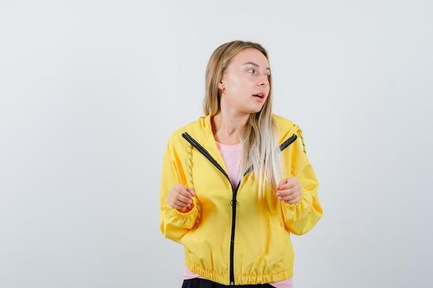 脇を見ながらきれいに見える黄色のジャケットのブロンドの女の子