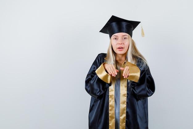 Ragazza bionda che invita a venire in abito e berretto da laurea e sembra amabile.