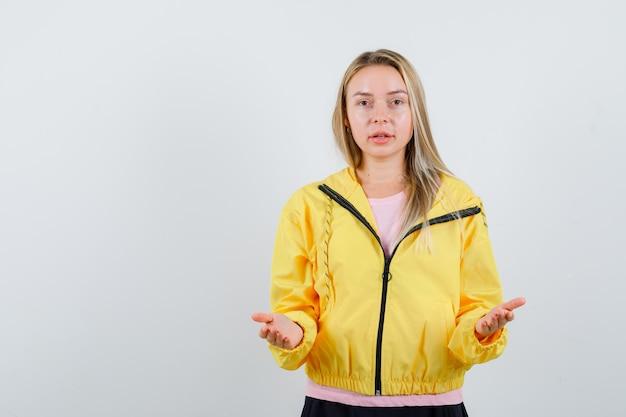 Светловолосая девушка в розовой футболке и желтой куртке приглашает зайти и выглядит мило.