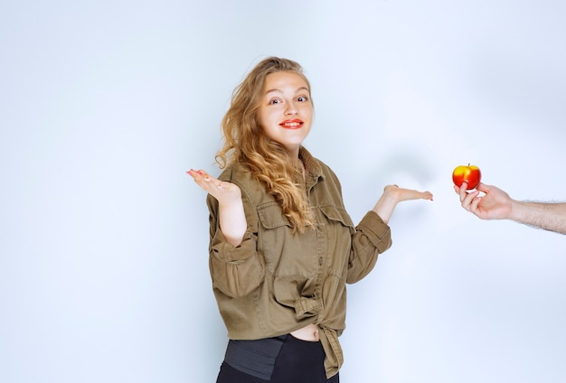 Блондинке предлагают красное яблоко или персик.