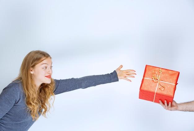 ブロンドの女の子は赤いギフトボックスを提供されており、彼女はそれを取ることを切望しています。