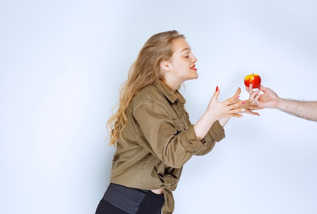 Blonde girl is being offered a red apple or peach.