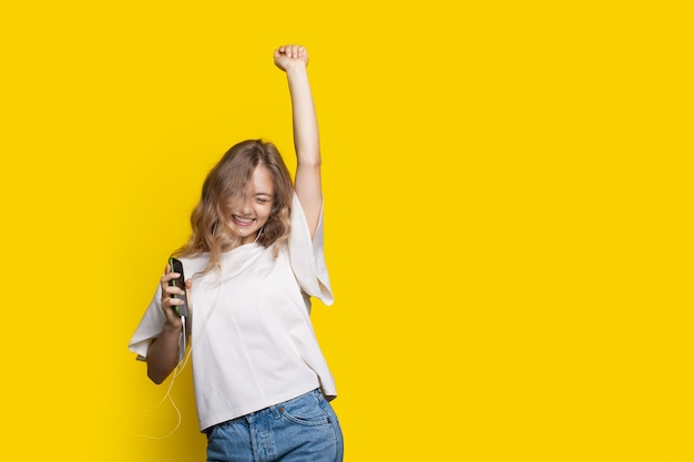 Blonde girl is cheering on a yellow wall with free space while listening to music on earphones and holding her hand up