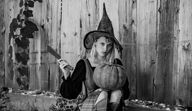 Blonde girl is preparing to carve a pumpkin