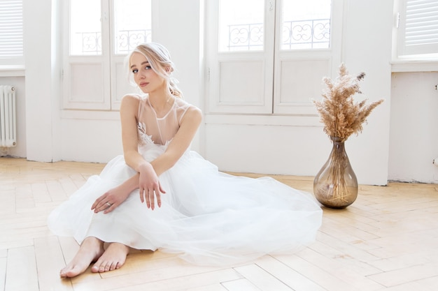 ブロンドの女の子は、美しい白いウェディングドレスで床に座っています。結婚式の前に女性の花嫁が新郎を待っています