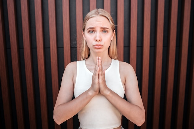 Blonde girl is standing at the wall and looking. she is keeping her hands in pray. young woman is upset and keeping her lips together.