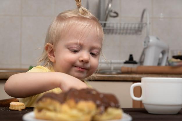 금발 소녀는 부엌에서 쿠키를하고있다. 아이와 과자.